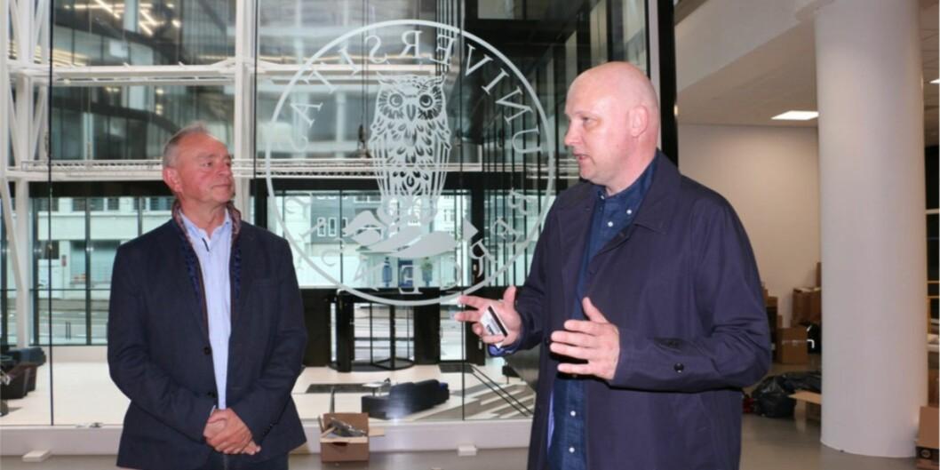 """Kjell Øvre Helland (til venstre) og Ole J. Mjøs viser rundt i Media City Bergen (<span class=""""caps"""">MCB</span>), som blir tatt i bruk nå i august. Universitetet er førstemann til å flytte inn. De er godt fornøyde med at UiB-logoen er den mest synlige fra den store foajeen. Foto: DagHellesund"""
