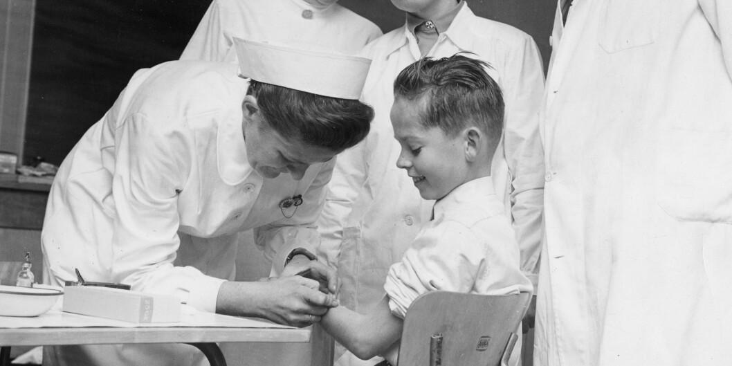 Nes på Romerike i 1956: Den første vaksineringen mot poliomylitt startet ved Framtun skole ved Nes på Romerike. Helsesøster Ruth Hauge vaksinerer den første eleven Ola Eide. Distriktslege Øverland og sykepleierskene Borghild Henden og Signe Berg følgermed. Foto: Storløkken, Aage