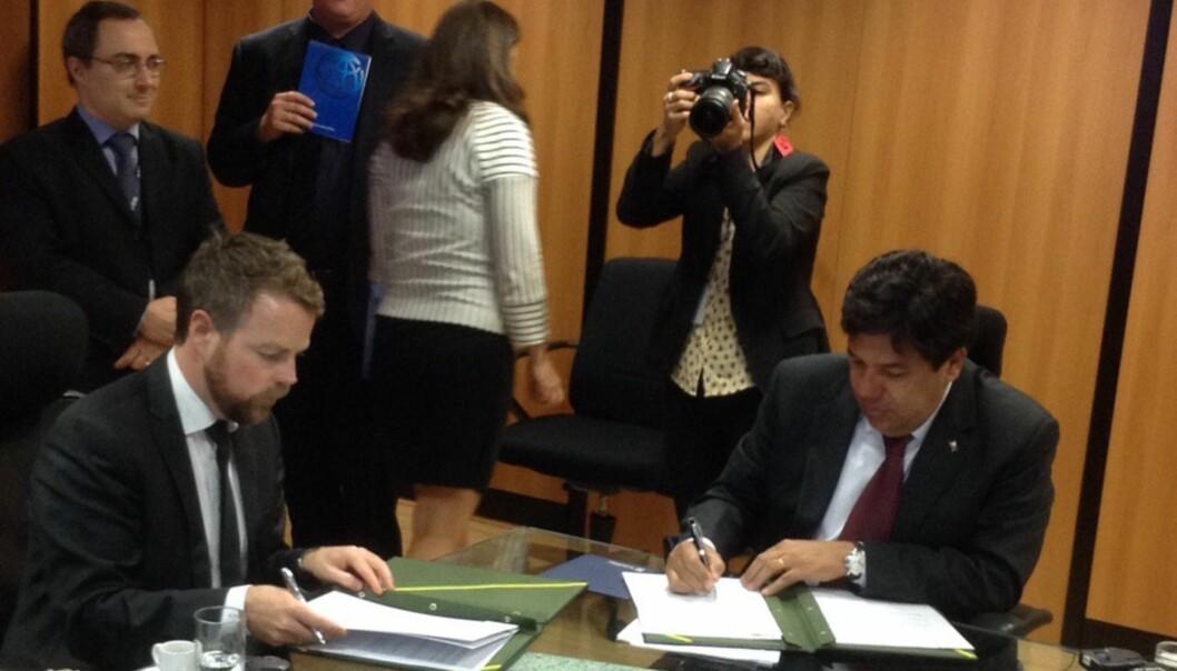 Isaksen signerer avtale med sin kollega i Brasil. (Foto: Dag Rune Olsen,Twitter)