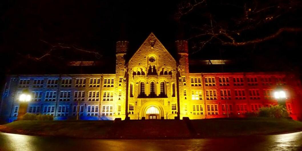 """<span class=""""caps"""">NTNU</span> har skapt mange gode lesesaker for Khrono i året som gikk. Både gjennom rangeringer der det har svingt fra topp til bunn, men også gjennom fusjonsarbeidet med de tre høgskolene Sør-Trøndelag, Ålesund og Gjøvik. Fra 1. januar 2016 er de Norges største universitet. Her ser vi hovedbygningen dandert i det franske flaggets farger for å markere støtte til ofrene for terroren som rammet i Paris. Foto: <span class=""""caps"""">NTNU</span>"""