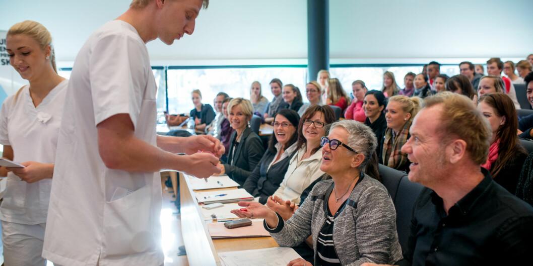 Finalistene Fredrik Arne Larsen og Areti Malakis fra gruppe 1 med løsningen «Team hjerterom» deler ut sjokoladehjerter til juryen. Prorektor Olgunn Ransedokken (i midten) blir også«bestukket». Foto: Skjalg Bøhmer Vold