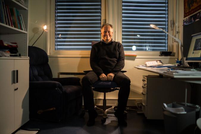 Khronos filmanmelder Jan Storø på kontoret hans på OsloMet. Han bruker aldri taklampene på kontoret, og foretrekker små lyskilder. Foto: David Engmo