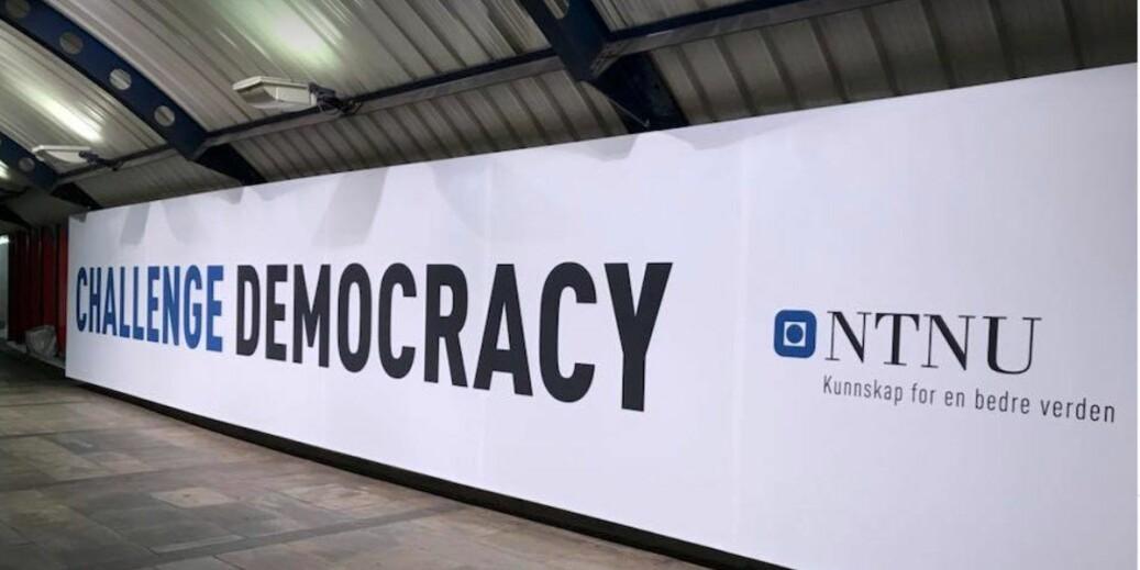 En svær plakat om å «utfordre demokratiet», med NTNU som avsender, har fått plass på Stortinget T-banestasjon i Oslo. Kampanjen vekker reaksjoner hos NTNUs egne ansatte. Foto: Tove Lie