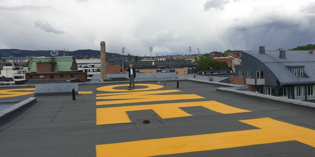 OsloMet-logoen finnes nå også på den femte fasade; taket. Seniorrådgiver Vidar Holum i Avdeling for eiendom har tatt plass i den ene O-en. Foto: OsloMet
