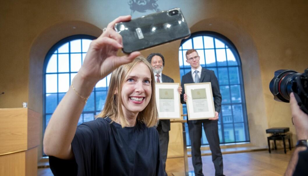 Forsknings- og høyere utdanningsminister, Iselin Nybø, benyttet sjansen til å ta en selfie med prisvinnerne Paul Gilroy og Finnur Dellsén i bakgrunnen. Foto: Tor Farstad