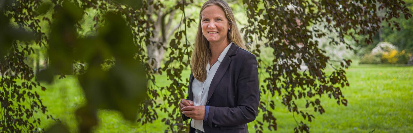 — Jeg tror og vi har kommet langt i å skape en stolthet for det å være en del av NMBU, sier Mari Sundli Tveit. Her står hun inne i et av de store trærne på campus Ås. Foto: Siri Øverland Eriksen