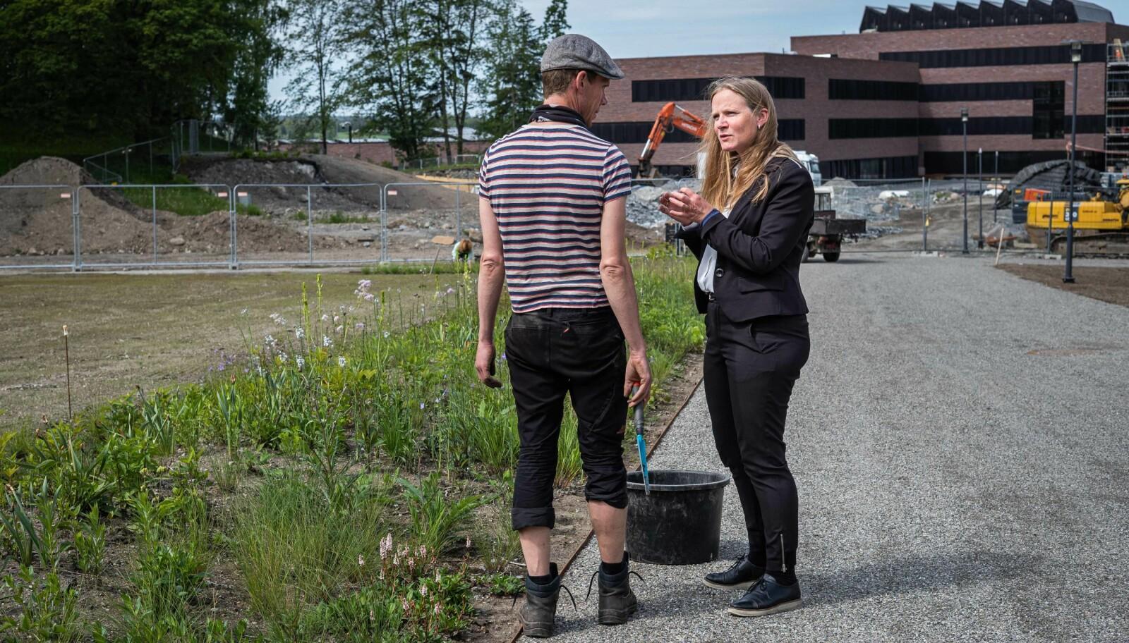 Mari Sundli Tveit prater med en gartner. Her skal det bli ny, fin hage. — Parkene er det jeg liker best med NMBU, sier Mari Sundli Tveit. Foto: Siri Øverland Eriksen.
