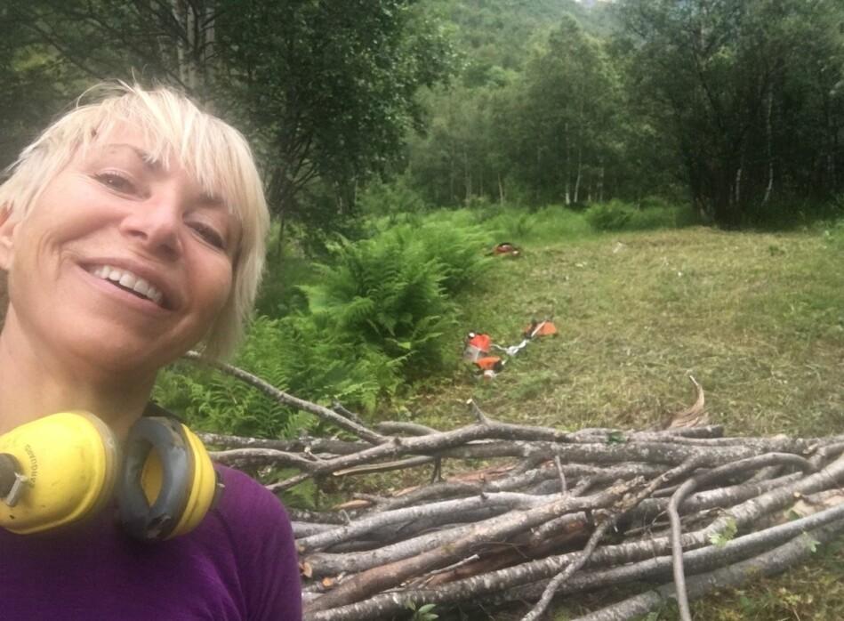 Med ryddesag og motorsag bygger Sissel Rogne muskler i naturen i ferien. Foto: Sissel Rogne