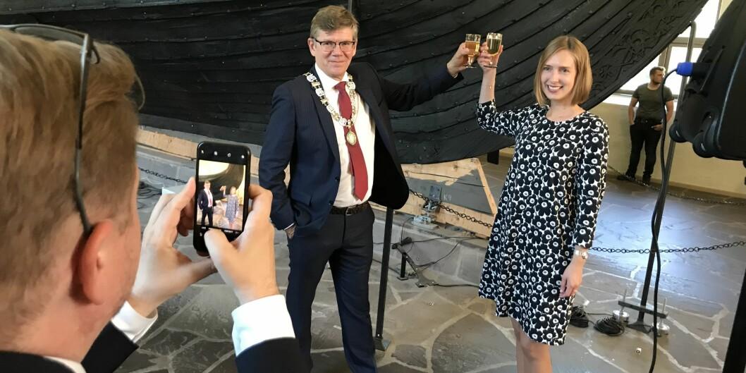 Svein Stølen og Iselin Nybø skåler i champagnebrus foran Osebergskipet. Stølen er forsatt lykkelig over at vikingtidsmuseet er inne på statsbudsjettet, men er bekymret for at det kommer andre nyheter som ikke er like gledelige for universiteter og høgskoler. Foto: Eva Tønnessen