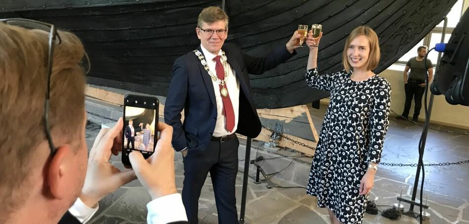 Svein Stølen og Iselin Nybø skåler i champagnebrus foran Osebergskipet. Foto: Eva Tønnessen