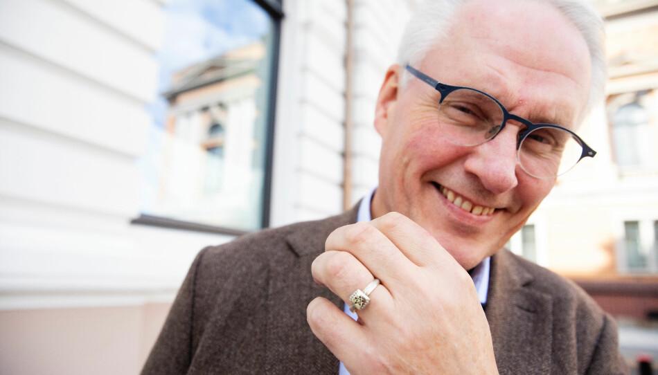 Gunnar Syverud viser fram NMBU-ringen som han har hatt på fingeren sidan han vart uteksaminert med landbruksutdanning i 1987. Foto: Ida Helene Andersen, Stortinget.