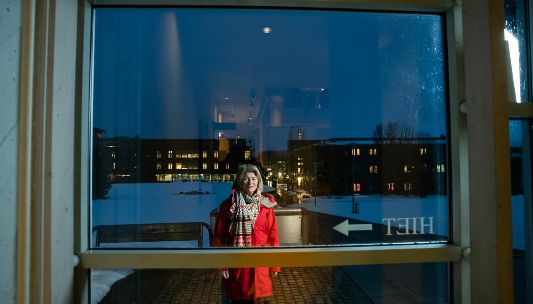 Rektor Anne Husebekk utenfor administrasjonsbygget på UiTs campus i Tromsø. Pilen peker til Hiet, som er navnet på et av rommene i bygget. Foto: Lars Åke Andersen