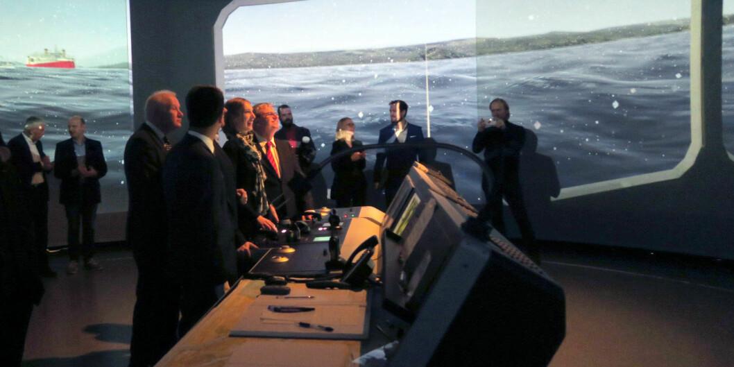 Statsråd Iselin Nybø tar styringen på det maritime simulatorlaboratoriumet på USN. Foto: USN