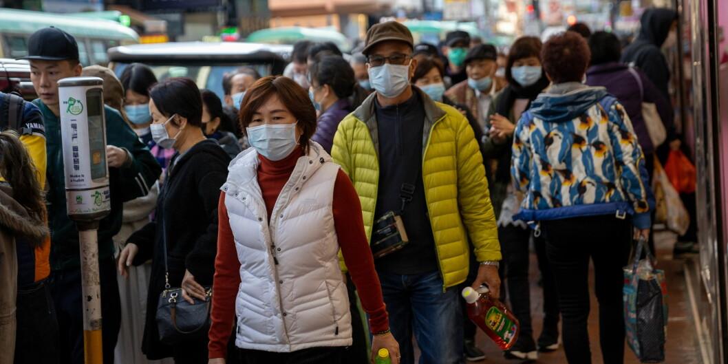 Folk i kø utenfor apotek i Tsuen Wan, Hong Kong, tirsdag denne uken. Nå henter Norge hjem nordmenn fra de rammede områdene. Foto: NTB scanpix