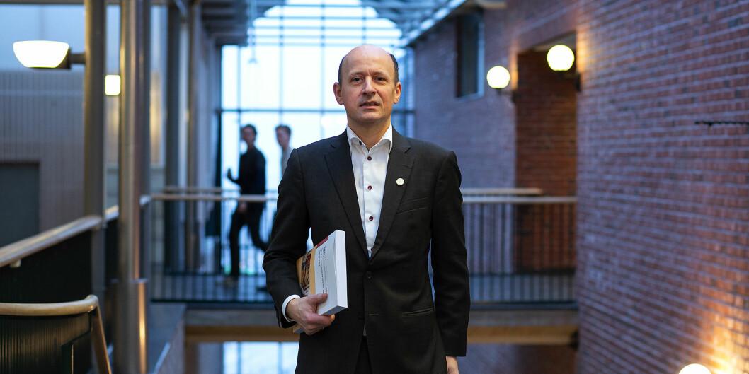 Kanskje ikke akkurat sengelektyre... Jussprofessor Karl Harald Søvig med den norske, offentlige utredningen om ny universitets- og høgskolelov under armen. Foto: Silje Robinson