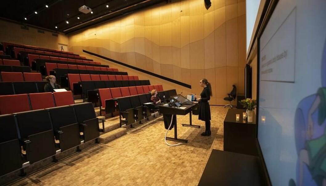 Maria Pain disputerer foran et tomt auditorium. Disputasen holdes under strenge restriksjoner i forbindelse med koronautbruddet . Pain er likevel en del av det rekordstore antallet som avla doktorgrader i pandemiåret 2020.