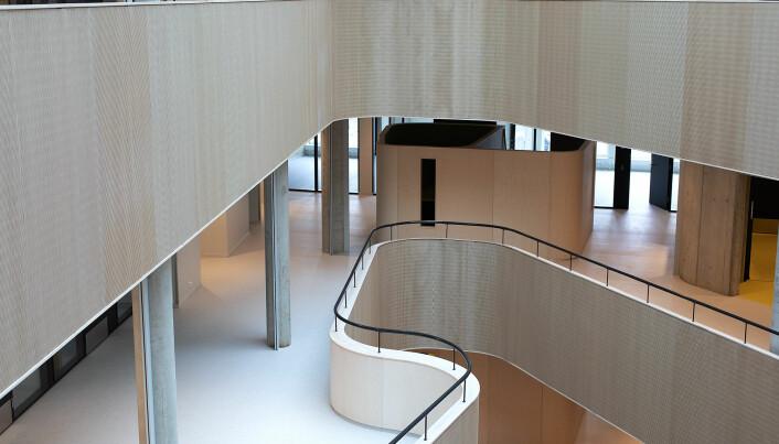"""Det lyse bygget har ulike typar arbeidsplassar. I """"boksen"""" midt i biletet finn ein studentarbeidsplassar. Dei har knall grøn eller knall gul innreiing, dei same fargane går att mellom anna i detaljar og i trapperom. Metropolis Arkitektur og design har hatt ansvar for interiøret, saman med L2 Arkitekter."""