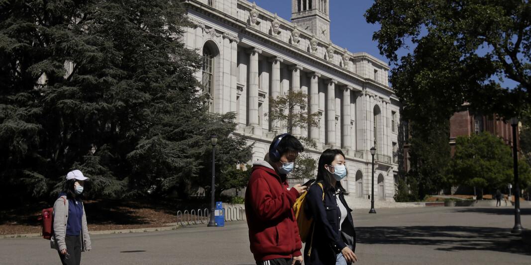 Folk med maske utenfor University of California, Berkeley, i mars. Universitetet er et av mange som har fått gruppesøksmål mot seg.