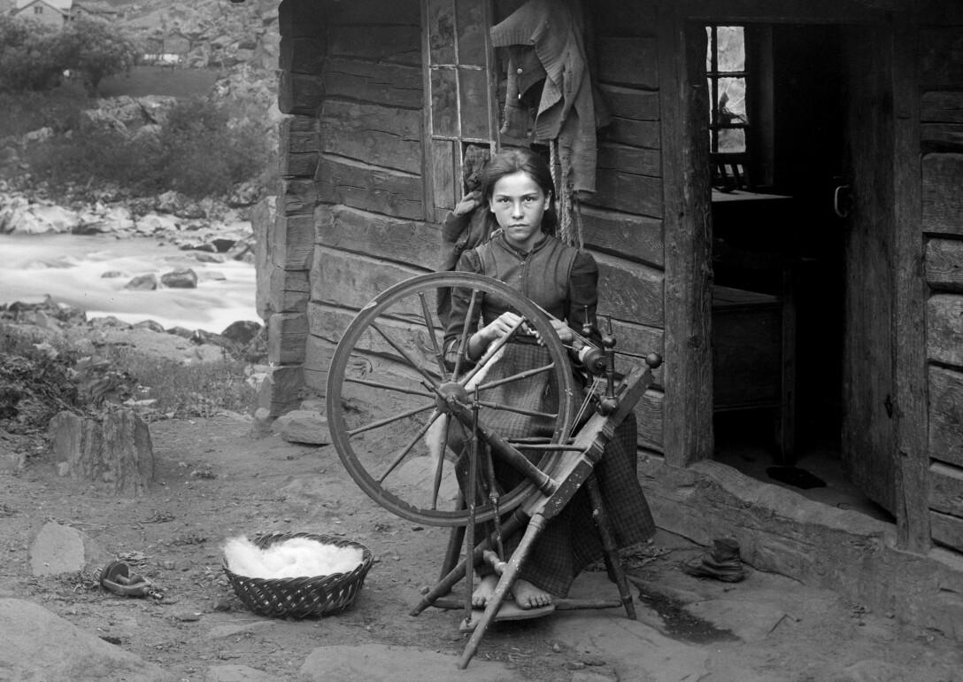 «Parti ved Sæltun, mellem Blaaflaten og Husum, Lærdal». Ein tittel som ikkje seier noko om at biletet av jenta ved rokken er fotografert på husmannsplassen Midtre Syne i Lærdal, truleg i slutten av 1880-åra. Ubb-kk-1622-09767.