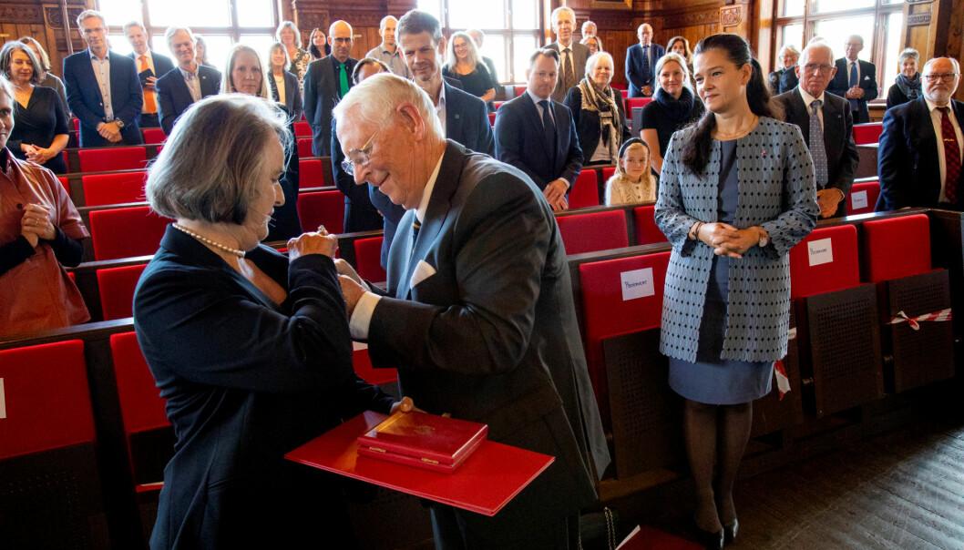 Professor emerita Brit Salbu er utnevnt til Ridder 1. klasse av Den Kongelige Norske St. Olavs Orden. Her får hun medaljen overrekt av sin ektemann Christoffer Aasland. Til høyre kanselier Mette Tverli fra Slottet.