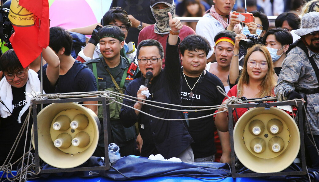 Her protesterer menneskerettsadvokaten Anon Numpa (med mikrofon) sammen med blant andre Parit Chiwarak (til høyre i bildet for Numpa) og Panusaya Sithijirawattanakul (til høyre i bildet for Chiwarak). Bildet er tatt onsdag 14. oktober, bare kort tid før de to sistnevnte skal ha blitt pågrepet.