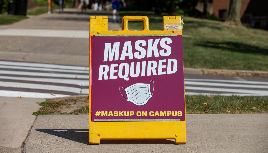 Et skilt ved Bloomsburg University minner folk om å bruke munnbind på campus. Pandemien har slått hardt inn i amerikanske universiteter.