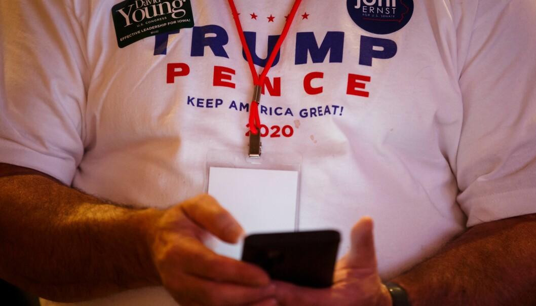 Folk følger med på telefonene mens resultatene kommer inn under en valgvake for republikanerne i Iowa.