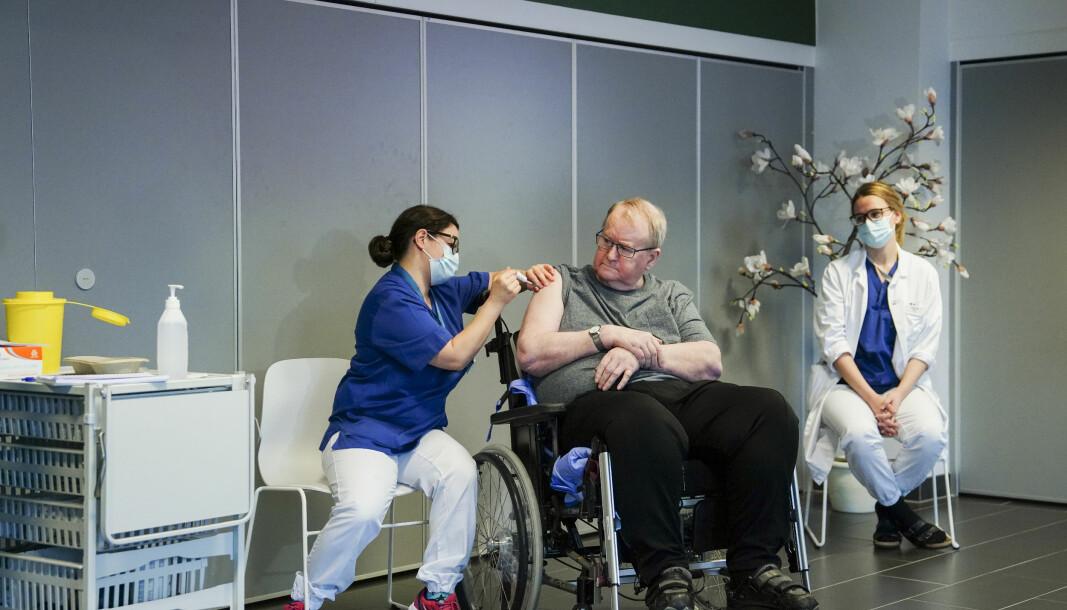 Sykepleier Maria Golding vaksinerer Svein Andersen (67) mot koronaviruset (Covid-19). Svein Andersen (67) beboer på Ellingsrudhjemmet var den første i Norge som fikk vaksinen 27.desember 2020. Lege er Ingvild Glende Svanstrøm sitter til høyre. Foto: Fredrik Hagen / NTB