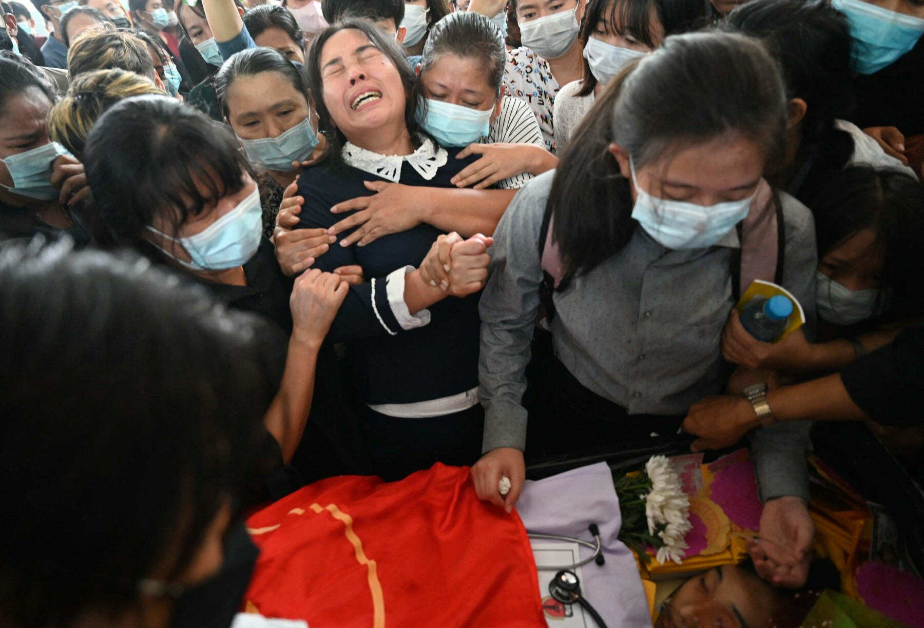 EDITORS NOTE: Graphic content / The mother (C) of Khant Nyar Hein reacts next to his body at the funeral in Yangon on March 16, 2021, after the first year medical student was shot dead during a crackdown by security forces on protesters taking part in a demonstration against the military coup. (Photo by STR / AFP)
