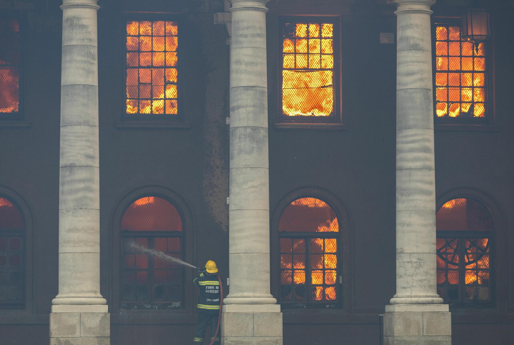 En brannmann slåss mot flammene i det nær 200 år gamle biblioteket ved Universitetet i Cape Town.