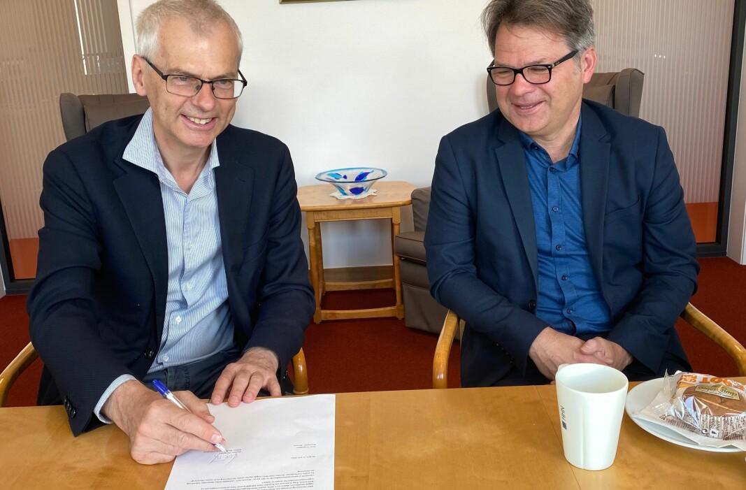 Rektor Øystein Thøgersen (til venstre) signerer på papirene som sier at også NHH nå er med på å finansiere kunnskapsavisen Khrono. Her sammen med styreleder i Khrono, Tore Tungodden .