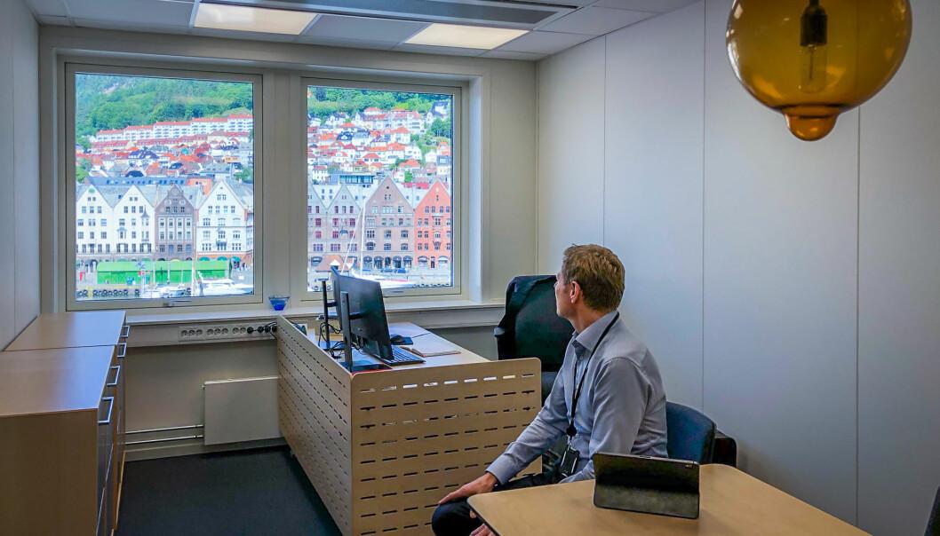 Sveinung Skule på sitt nye kontor i Bergen, med utsikt over bryggen.